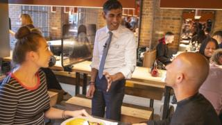 Chancellor Rishi Sunak speaks to diners at a Wagamamas restaurant