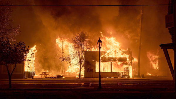Buildings are engulfed in flames as a wildfire ravages Talent, Ore., on Sept. 8, 2020. Unfounded rumors that left-wing activists were behind the fires went viral on social media, thanks to amplification by conspiracy theorists and the platforms