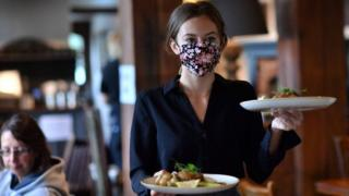 Waitress carries tray of food