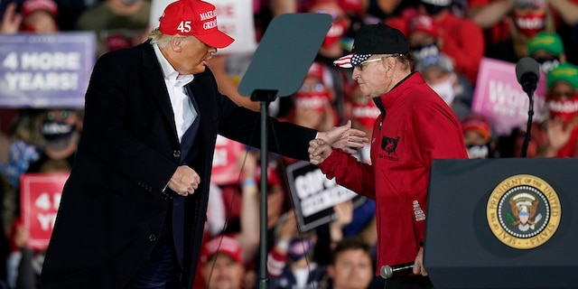FILE - In this Oct. 14, 2020 file photo, President Donald Trump greets former University of Iowa wrestling coach Dan Gable, right, during a campaign rally at Des Moines International Airport in Des Moines, Iowa. (AP Photo/Charlie Neibergall)