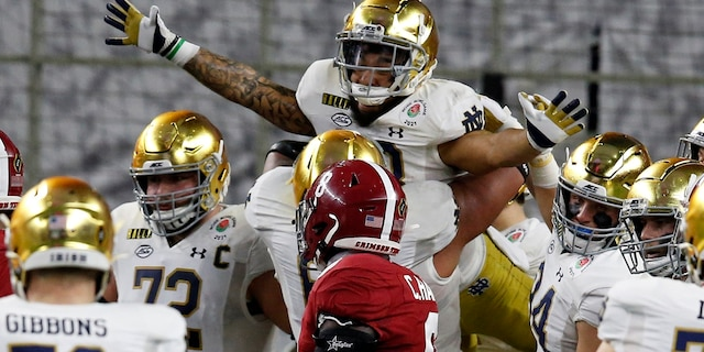 Notre Dame running back Kyren Williams, top, is lifted by offensive lineman Landon Dickerson (69) after Williams' touchdown run as Alabama linebacker Christian Harris (8) looks on in the first half of the Rose Bowl NCAA college football game in Arlington, Texas, Friday, Jan. 1, 2021. (AP Photo/Roger Steinman)