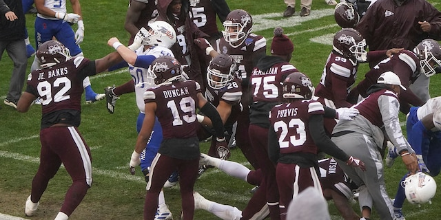 Members of Tulsa and Mississippi State fight after time runs out in the Armed Forces Bowl NCAA college football game Thursday, Dec. 31, 2020, in Fort Worth, Texas. (AP Photo/Jim Cowsert)