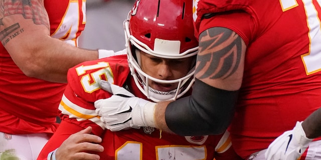 Kansas City Chiefs quarterback Patrick Mahomes (15) is helped off the field by teammate Mike Remmers, right, after getting injured during the second half of an NFL divisional round football game against the Cleveland Browns, Sunday, Jan. 17, 2021, in Kansas City. (AP Photo/Charlie Riedel)