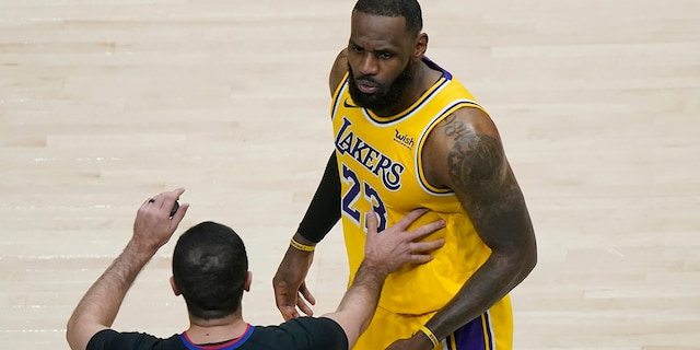 Los Angeles Lakers forward LeBron James (23) is restrained by an official as he reacts to a fan in the second half of an NBA basketball game against the Atlanta Hawks, Monday, Feb. 1, 2021, in Atlanta. (AP Photo/John Bazemore)