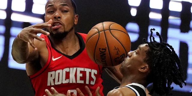 Los Angeles Clippers guard Terance Mann, right, loses control of the ball while under pressure from Houston Rockets forward Sterling Brown during the second half of an NBA basketball game Friday, April 9, 2021, in Los Angeles. (AP Photo/Mark J. Terrill)