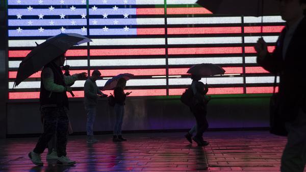 People holding umbrellas walk through New York City