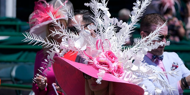 A women watches a race before the 147th running of the Kentucky Oaks at Churchill Downs, Friday, April 30, 2021, in Louisville, Ky.(AP Photo/Michael Conroy)