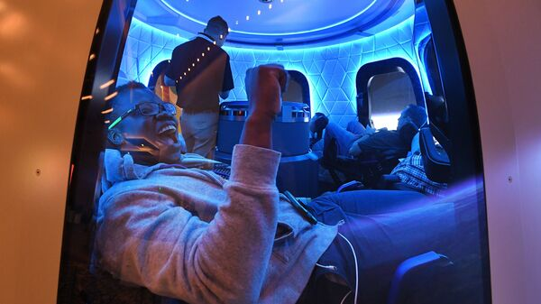 Participants sit a Blue Origin space simulator during a conference on robotics and artificial intelligence in Las Vegas on June 5, 2019. On Saturday, Blue Origin announced that an unidentified bidder will pay $28 million for a suborbital flight on the company