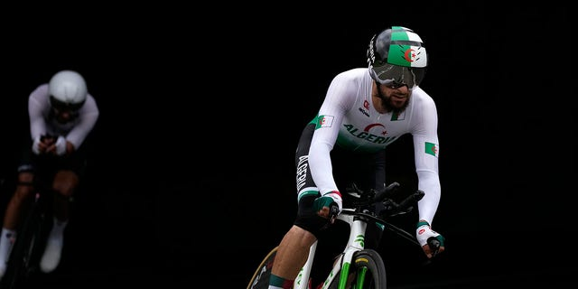 Azzedine Lagab of Algeria, right, and Ahmad Badreddin Wais of the Olympic Refugee Team, compete during the men's cycling individual time trial at the 2020 Summer Olympics, Wednesday, July 28, 2021, in Oyama, Japan. (AP Photo/Christophe Ena)