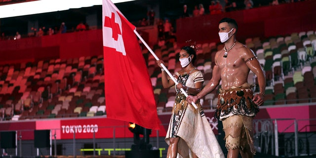 Malia Paseka and Pita Taufatofua, of Tonga, carry their country's flag during the opening ceremony in the Olympic Stadium at the 2020 Summer Olympics, Friday, July 23, 2021, in Tokyo, Japan. (Hannah McKay/Pool Photo via AP)