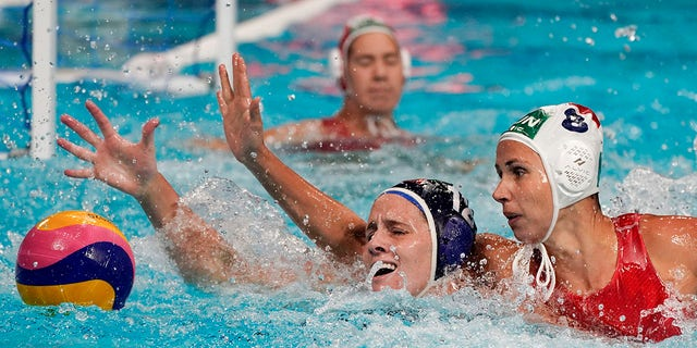 United States' Alys Williams (12) and Hungary's Rita Keszthelyi (8) reach for the ball during a preliminary round women's water polo match at the 2020 Summer Olympics, Wednesday, July 28, 2021, in Tokyo, Japan. (AP Photo/Mark Humphrey)