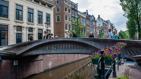 The almost 40-foot 3D-printed pedestrian bridge designed by Joris Laarman and built by Dutch robotics company MX3D has been opened in Amsterdam six years after the project was launched. The bridge, which was fabricated from stainless steel rods by six-axis robotic arms equipped with welding gear, spans the Oudezijds Achterburgwal in Amsterdam