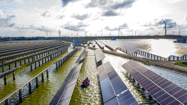 Electrical workers check solar panels at a photovoltaic power station built in a fishpond in Haian in China