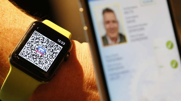 A person scans a QR Code on an Apple Watch to send a digital driver